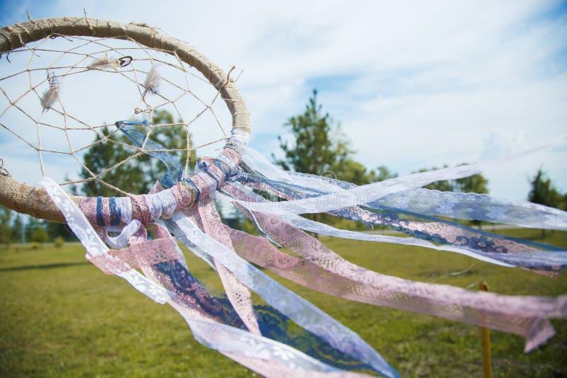Dreamcatcher dichte omhooggaand op een achtergrond van groen gras en blauwe hemel stock foto