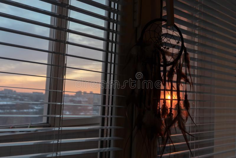 Dreamcatcher fait main accrochant par la fenêtre avec des abat-jour au crépuscule de coucher du soleil Silhouette noire d'amulett image stock