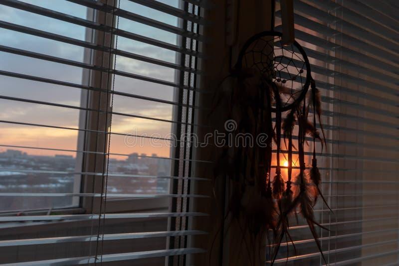 Dreamcatcher fatto a mano che appende dalla finestra con i ciechi nella penombra di tramonto Siluetta nera dell'amuleto magico tr immagine stock