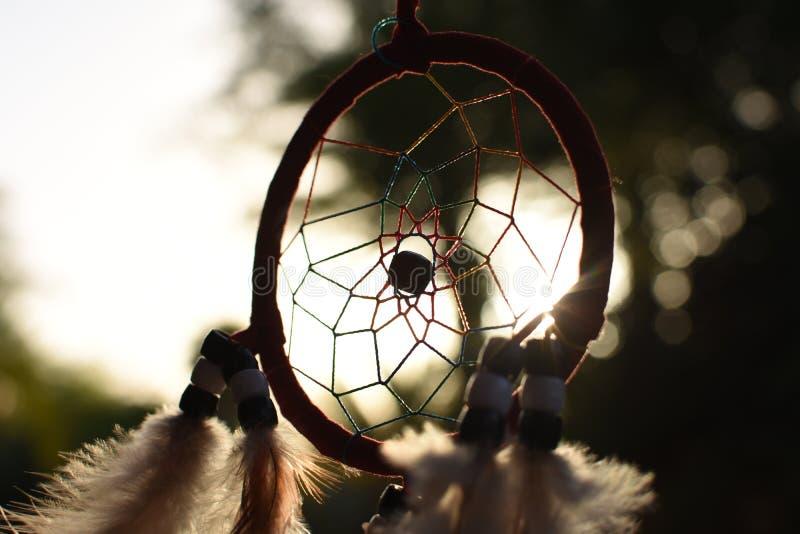 Dreamcatcher indiano della mascotte sui precedenti del tramonto e sul fogliame degli alberi fotografia stock libera da diritti