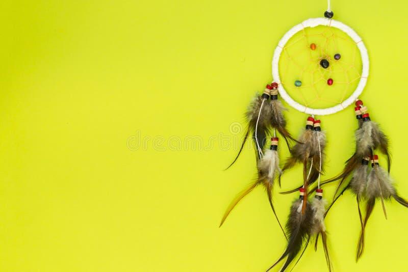 Dreamcatcher med bruna f?gelfj?drar och med tr?dar och p?rlor av att h?nga f?r rep Handgjorda Dreamcatcher L?gner p? en gr?splan royaltyfri foto