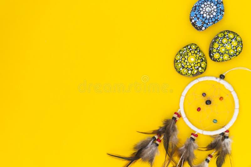 Dreamcatcher med bruna f?gelfj?drar och med tr?dar och p?rlor av att h?nga f?r rep Handgjorda Dreamcatcher Det ligger på en gulin arkivbild