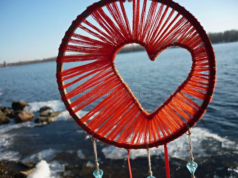 Dreamcatcher na forma de um cora??o na perspectiva do rio Por do sol de Dreamcatcher, montanhas, boho-chique, amuleto ?tnico imagens de stock