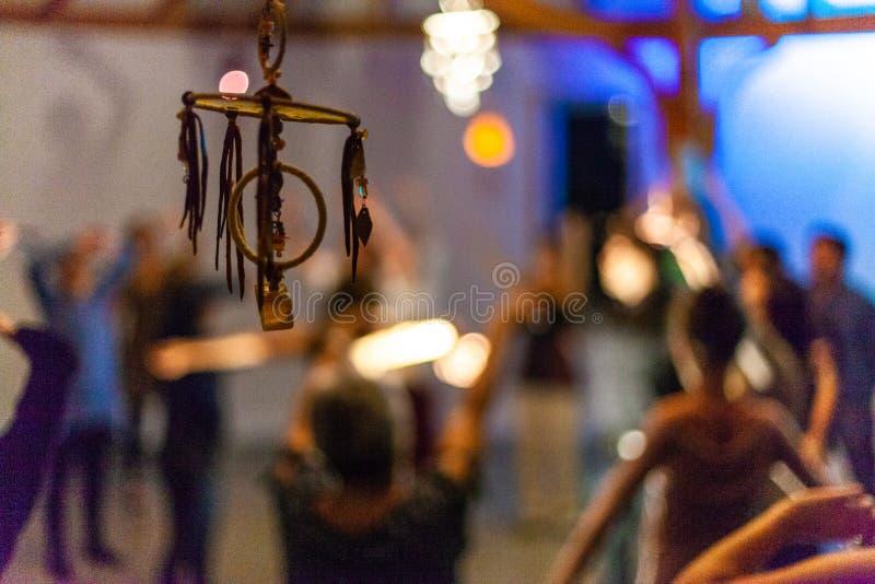 Dreamcatcher som framme ses av en grupp människor som inomhus dansar royaltyfri fotografi