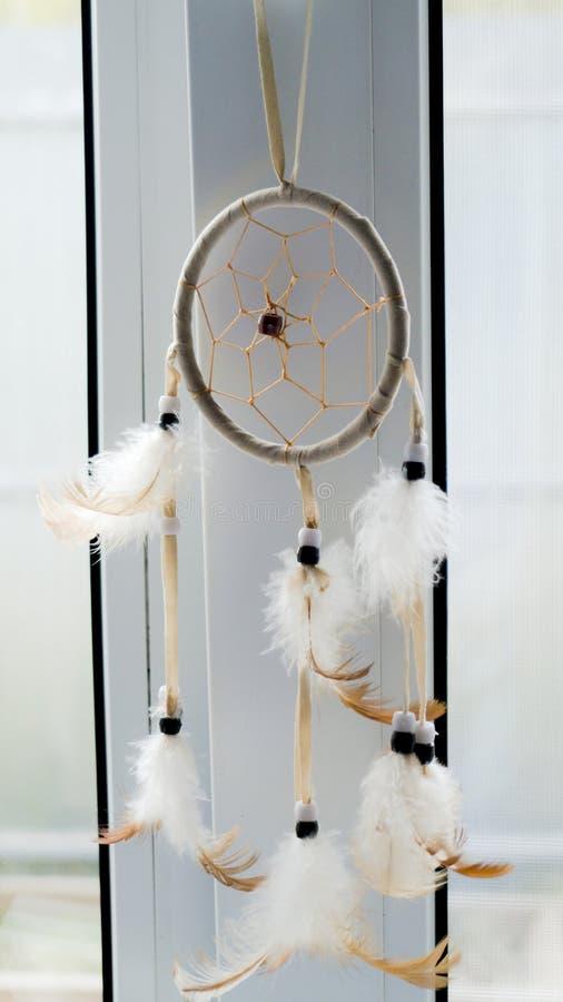 Dreamcatcher som hänger på fönstret Vitt och ljust - brunt royaltyfri foto