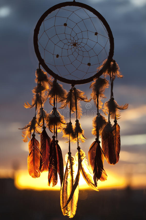 Dreamcatcher. A dreamcatcher on window with sunset on the bachground