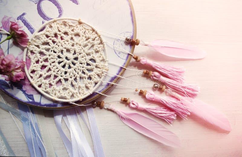 Dreamcatcher z menchii różami na drewnianym tle i piórkami zdjęcie royalty free