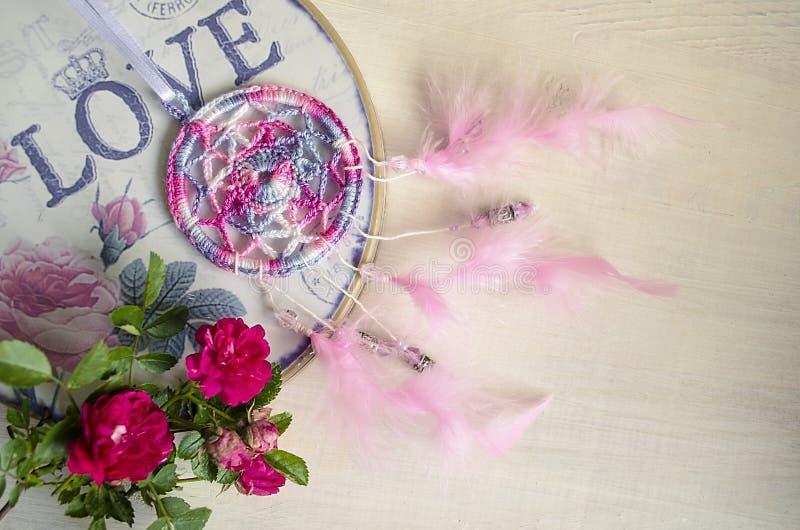 Dreamcatcher z menchii różami na drewnianym tle i piórkami zdjęcie stock