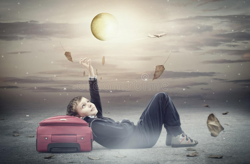Dreamer. Concept illustrating a little boy trying to reach to the moon stock photo