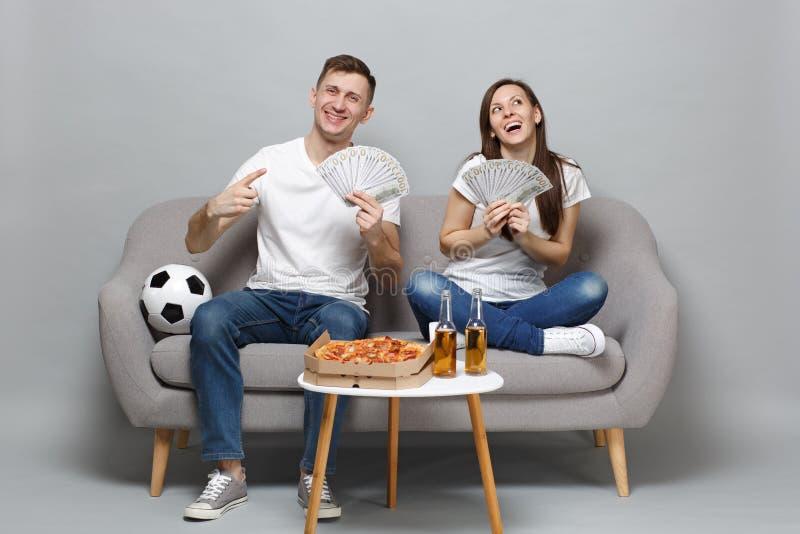 Dreamful夫妇妇女人足球迷在美元钞票使支持拿着金钱,现金的爱好者喜爱队振作 免版税库存照片