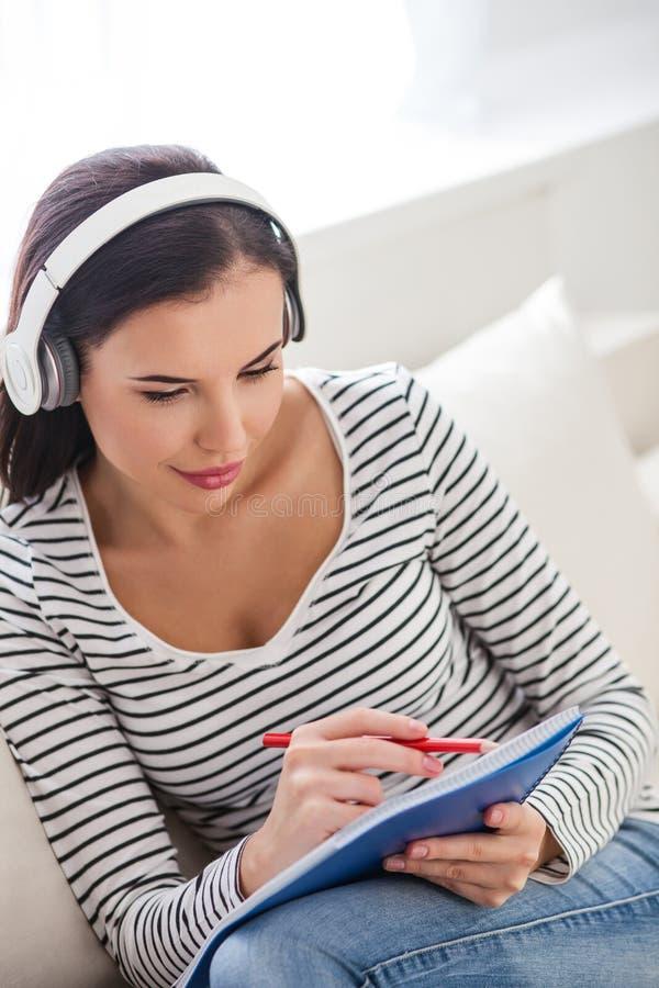Dreamful-Mädchen, das Musik während der Studie hört stockbilder