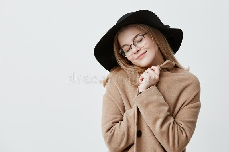 Dreamful positive female in retro outfit, wraps in coat, stands against gray background with closed eyes, imagines royalty free stock image