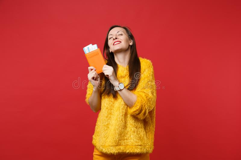 Dreamful woman in yellow fur sweater keeping eyes closed, holding passport, boarding pass ticket isolated on bright red royalty free stock images