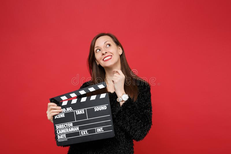 Dreamful young woman in black fur sweater looking up and holding classic black film making clapperboard isolated on red stock image