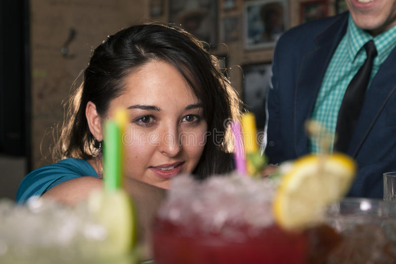 Dreamily woman looks at some cocktails in bar environment royalty free stock images