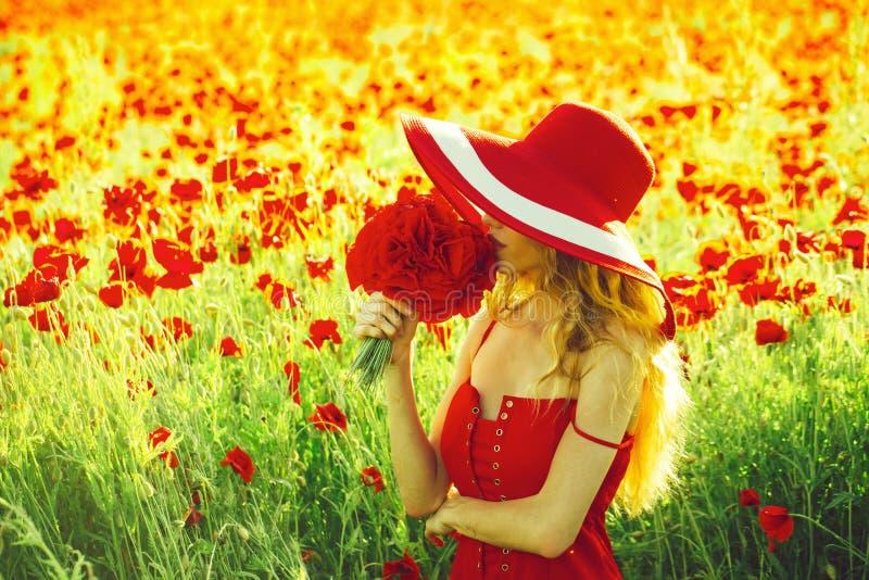 dreaminess mooi meisje met hoed op rood papavergebied stock foto