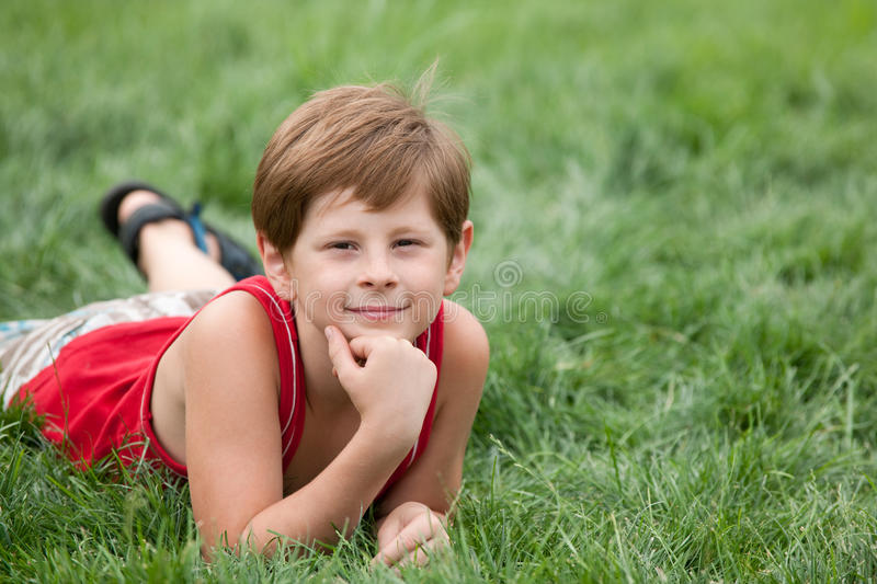 Dreaming boy on the green grass royalty free stock photography