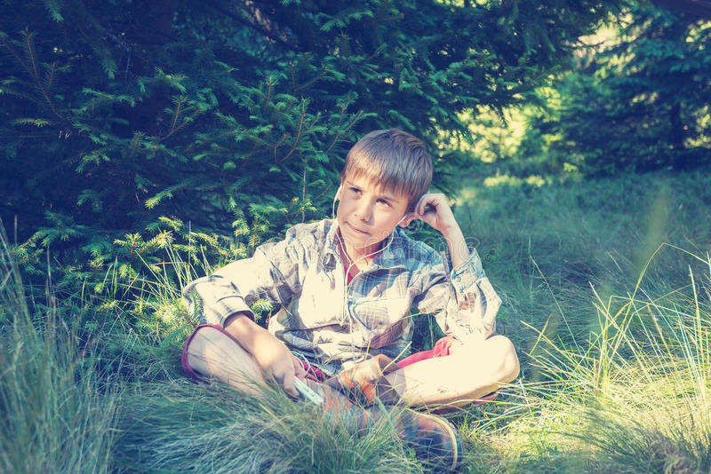 Dreaming boy in headphones sits in the lush grass stock photography
