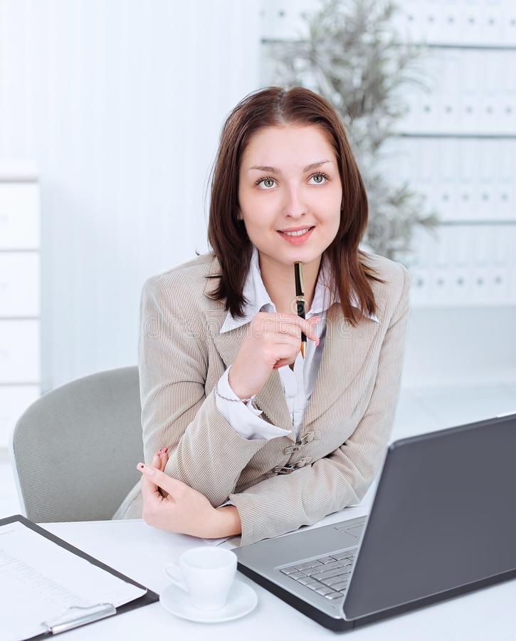 Dreaming business woman sitting at her Desk royalty free stock photo