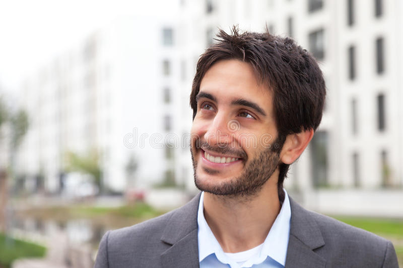 Dreaming businessman with black hair and beard in the city stock photo