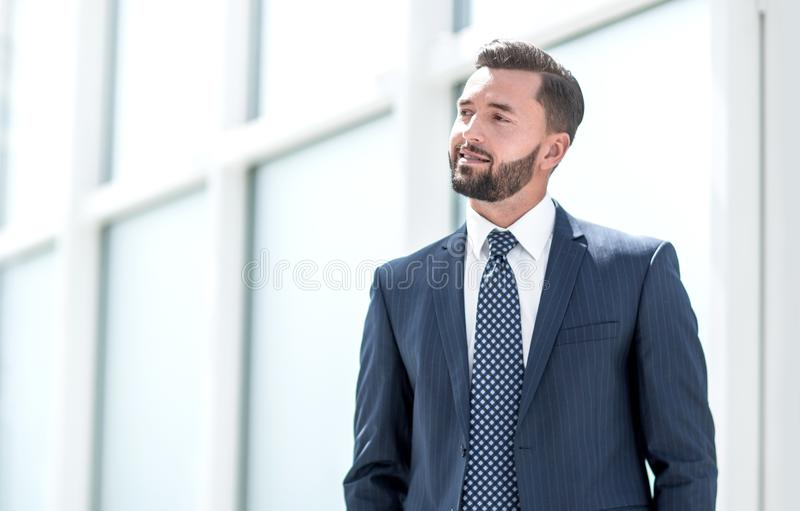 Dreaming businessman standing in a bright office. stock photography