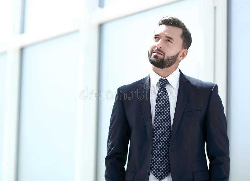 Dreaming businessman standing in a bright office. stock photos