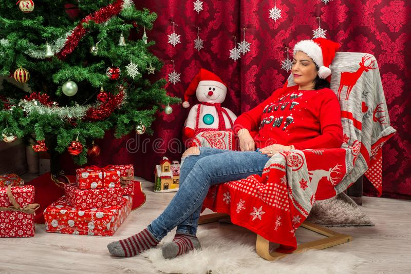 Dreaming Christmas woman in chair. Dreaming beauty woman sitting in chair near Christmas tree with gifts stock images