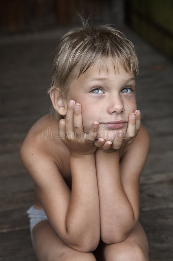 Dreaming country boy. Sitting on wooden steps royalty free stock image
