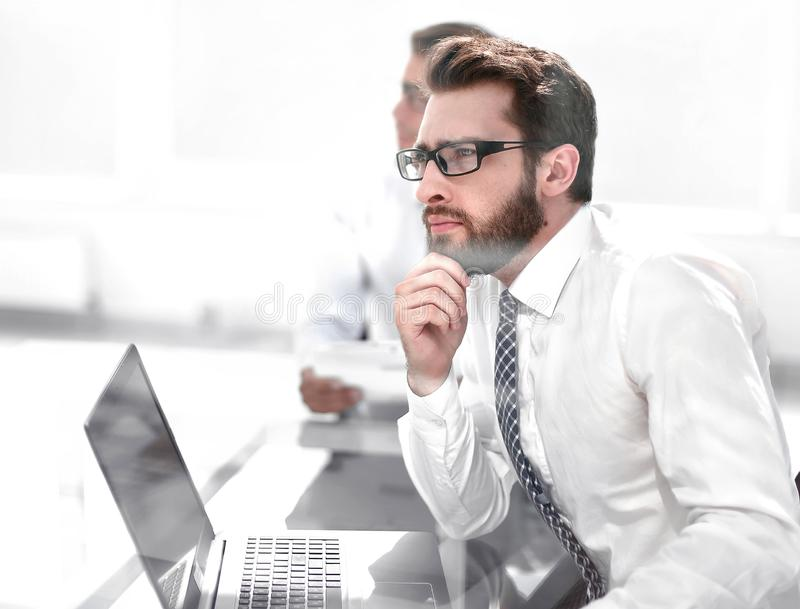 Dreaming employee sitting at the office Desk. Business concept stock image