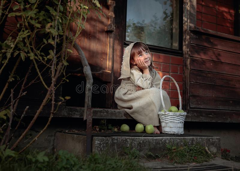 Dreaming girl with apples on a summer evening near the old house royalty free stock images