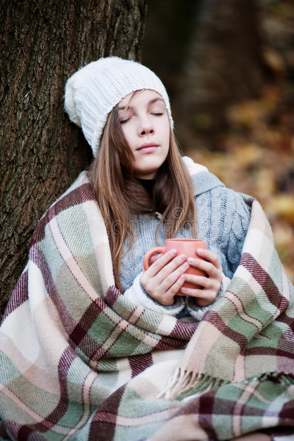 Dreaming girl with a plaid and a cup of tea stock photo