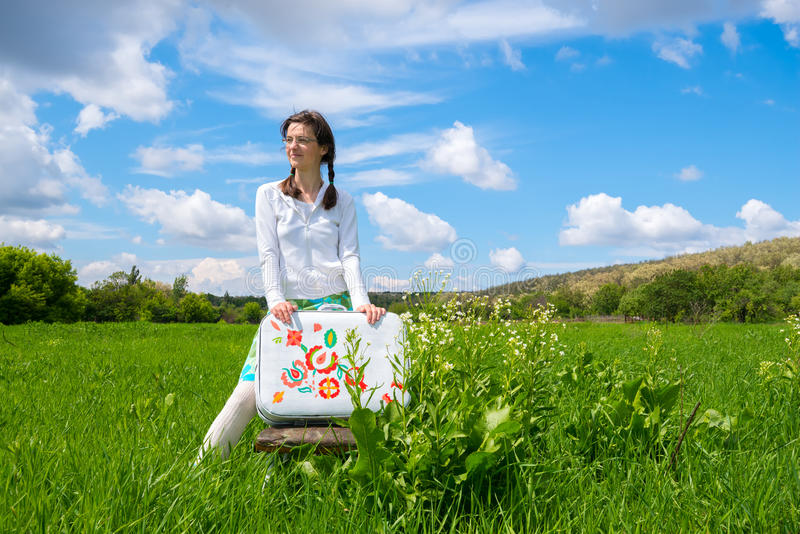 Dreaming girl standing in green field on clouds background stock images
