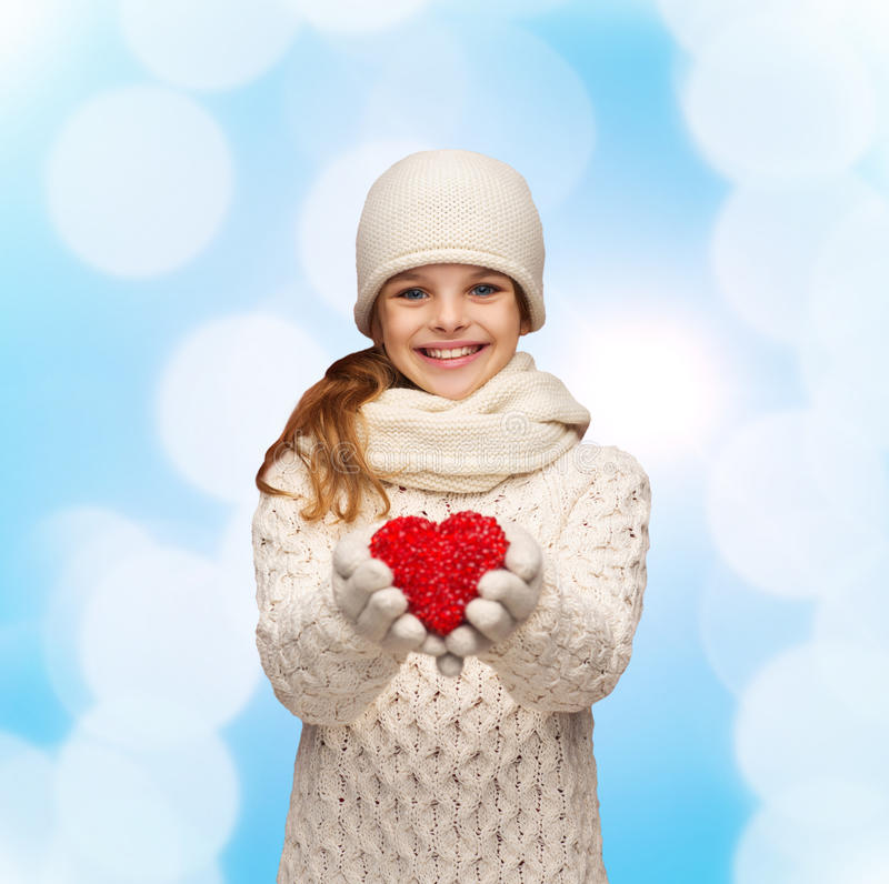 Dreaming girl in winter clothes with red heart royalty free stock photos