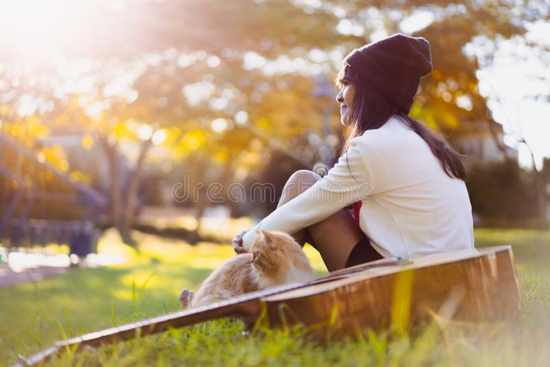 Dreaming little girl. Young asian girl sitting in the park with her kitten stock photography