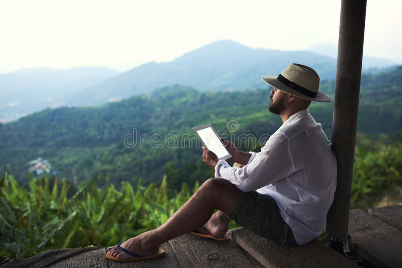Dreaming man is holding touch pad with copy space on screen, while is enjoying amazing jungle view. Male author is admiring beautiful Asian scenery, while royalty free stock photo
