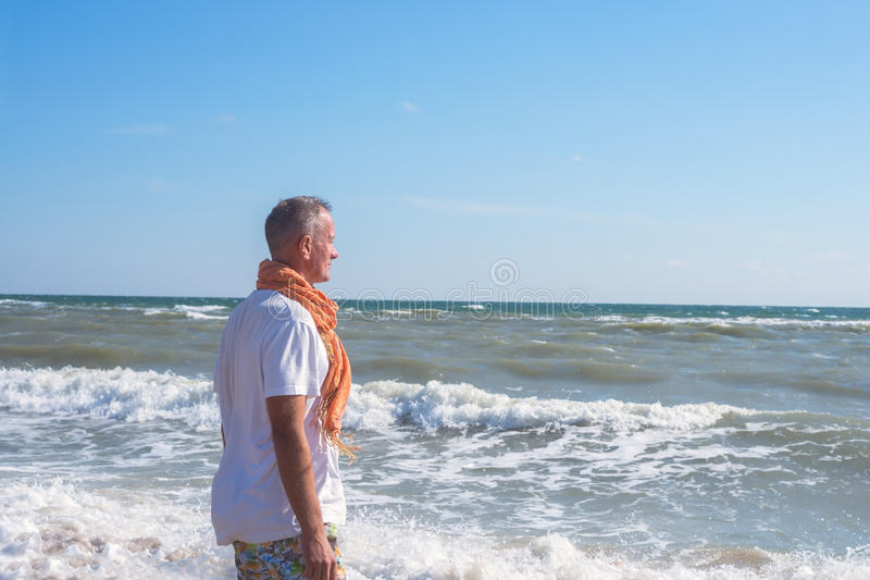 Dreaming man stands on the beach in surf line. And looks at the waves. Sunny windy day on the seaside royalty free stock photography