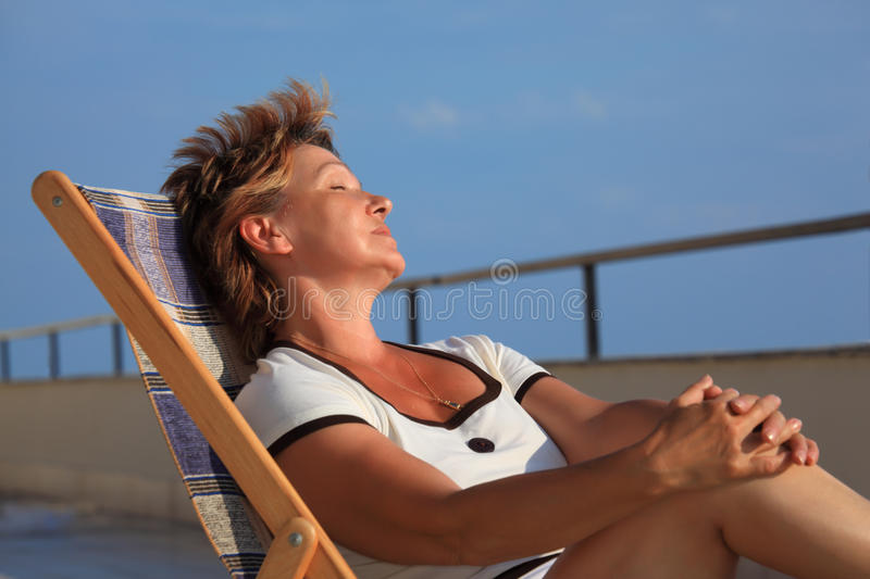 Dreaming middleaged woman in lounge on veranda. Over sea stock photo