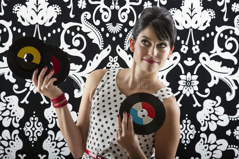 Dreaming of music. Young woman is stylist 60's inspired clothing, holding three vinyl records stock photography