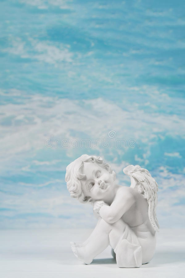 Dreaming or sad white angel on blue heaven background for a condolence card. royalty free stock photo