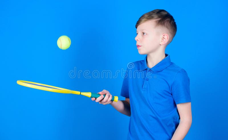 Dreaming about sport career. Athlete kid tennis racket on blue background. Tennis sport and entertainment. Boy child. Play tennis. Practicing tennis skills. Guy royalty free stock image