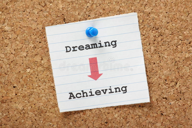 Dreaming to Achieving. An arrow pointing the way from Dreaming to Achieving on a paper note pinned to a cork board. We all have dreams,plans and goals but need royalty free stock images