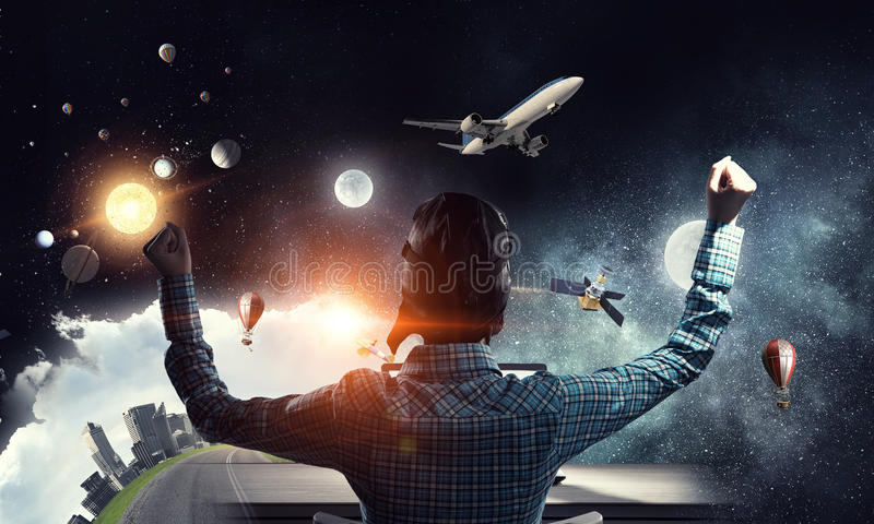 Dreaming to become pilot. Mixed media. Attractive girl gamer in pilot helmet playing on her laptop. Mixed media royalty free stock photography
