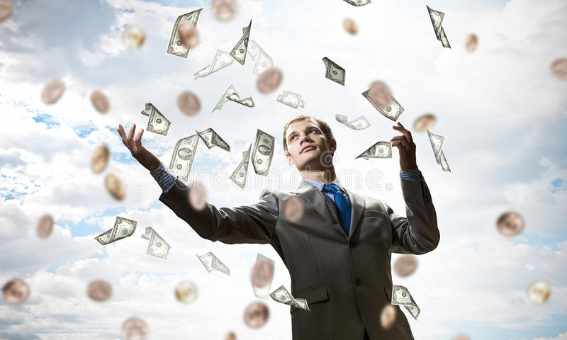 Dreaming to become rich . Mixed media. Young businessman standing in the rain of money banknotes royalty free stock photos