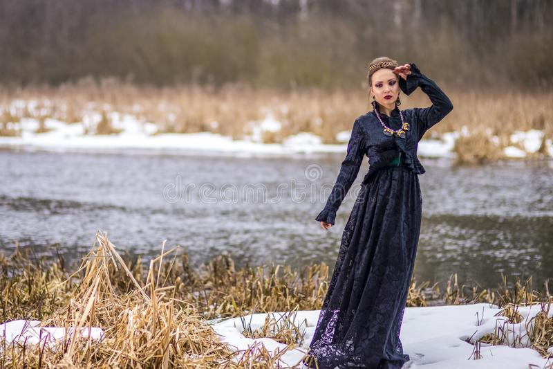Dreaming Vulnerable Caucasian Brunette Female in Art Dress with Necklace and Crown Posing Against River Outdoors stock photo