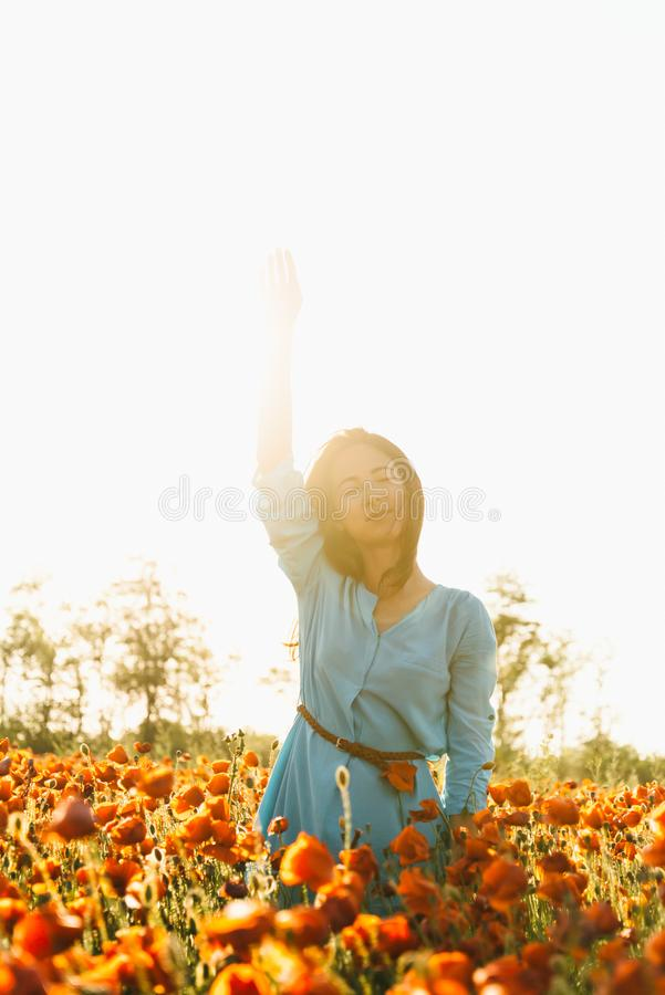 Dreaming woman enjoying of sunny day in poppy meadow. stock images