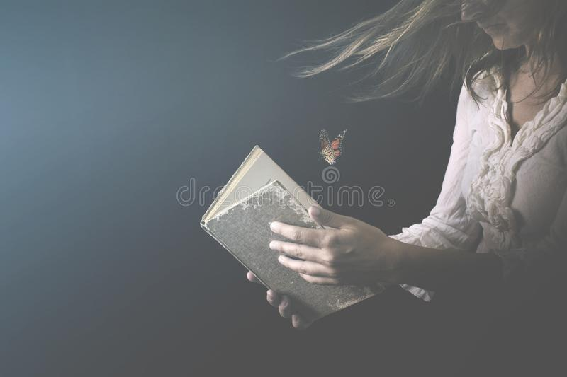 Woman reads a book where butterflies go out stock photography