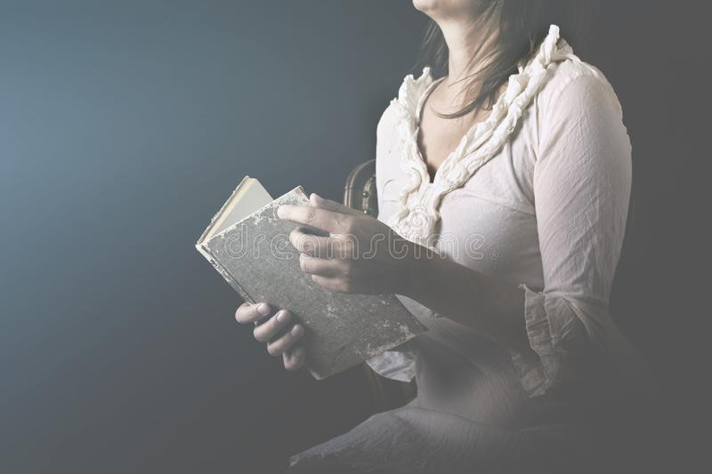 Dreaming woman reads the pages of a book with love stock photo