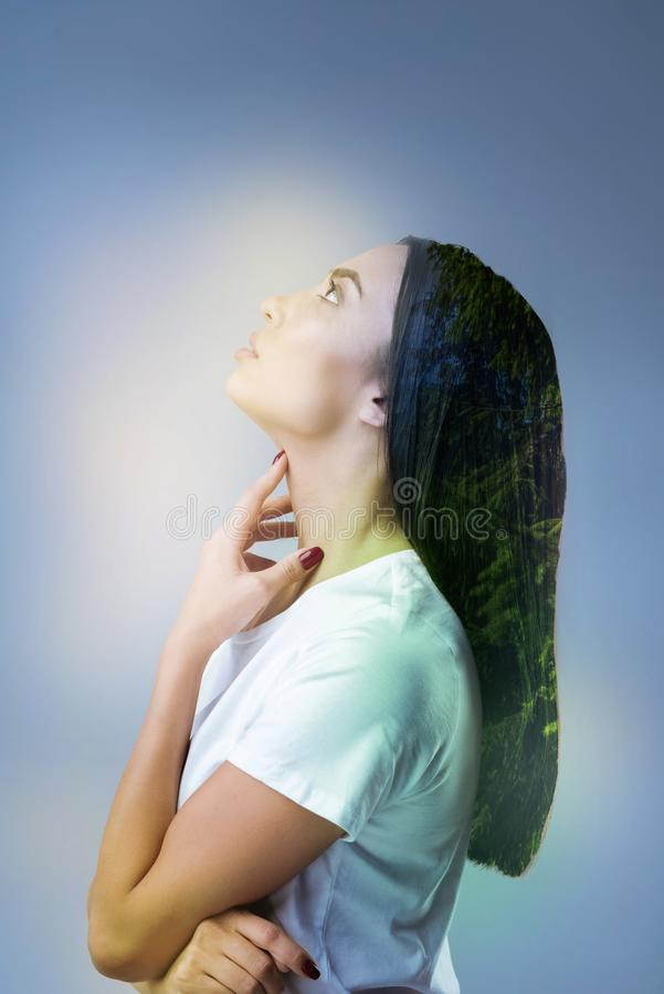 Attentive girl being deep in thoughts. Dreaming about you. Attractive brunette looking upwards and touching neck while being concentrated on her problem royalty free stock image