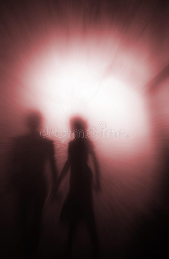 Dreaming of you. Couple walking in the park at night, illuminated from behind by a blurred distant lamp