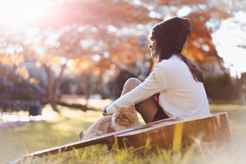 Dreaming. Young asian girl sitting in the park with her kitten and dreaming stock image